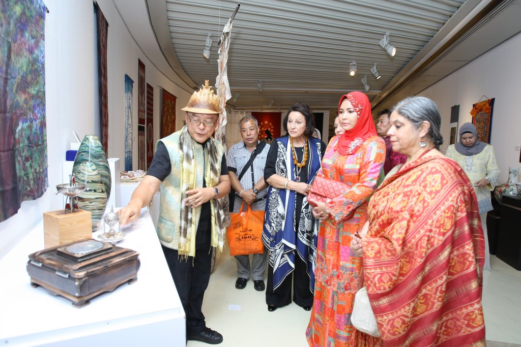 Curators of POHON BUDI exhibition, Edric Ong (left) and Manjari Nirula (right) showing the environmental artworks which potray the Tree-of-Life theme to KDYMM Sultanah Nur Zahirah