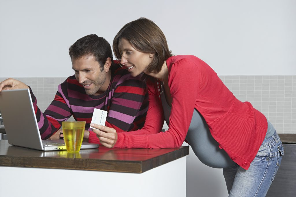 Man and Pregnant Woman Using Laptop
