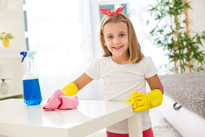 Adorable worth girl holding pom and cleaning a table at room