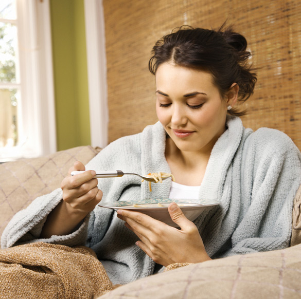 young-woman-sitting-on-a-couch-in-a-bathrobe-eating-soup